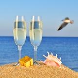 Vidrios de champán, de caja con un regalo y de seashel Imágenes de archivo libres de regalías