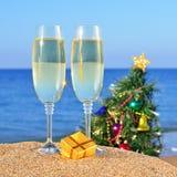 Vidrios del champán y del árbol de navidad en una playa Imágenes de archivo libres de regalías