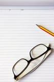 Vidrios del cuaderno, del lápiz y del ojo en el fondo de madera imagen de archivo libre de regalías