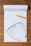 Vidrios del cuaderno, del lápiz y del ojo en el fondo de madera foto de archivo