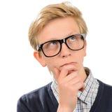 Vidrios del friki del muchacho pensativo del empollón que llevan Fotos de archivo libres de regalías