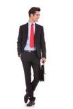 Vidrios del hombre de negocios y cartera el sostenerse que desgastan Fotografía de archivo