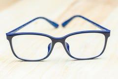 Vidrios del ojo azul en la tabla de madera para el negocio, diseño de concepto de la educación foto de archivo