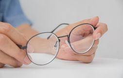 Vidrios del ojo de la tenencia de la mano de la mujer en la tabla blanca y el blanco fotografía de archivo libre de regalías