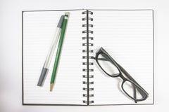 Vidrios del ojo de la visión superior con el cuaderno del lápiz, de la pluma y de la carpeta aislado en el fondo blanco Fotografía de archivo libre de regalías