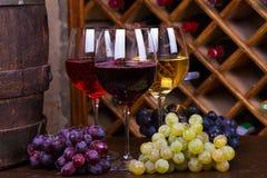 Vidrios del rojo, color de rosa y blancos con la uva en barril de madera viejo Imagen de archivo
