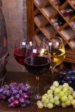 Vidrios del rojo, color de rosa y blancos con la uva en barril de madera viejo Foto de archivo libre de regalías