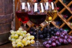 Vidrios del rojo, color de rosa y blancos con la uva en barril de madera viejo Imagenes de archivo