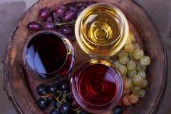 Vidrios del rojo, color de rosa y blancos con la uva en barril de madera viejo Visión desde arriba, tiro superior del estudio Imágenes de archivo libres de regalías
