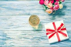 Vidrios del vino blanco, de flores y de un regalo Fotografía de archivo libre de regalías