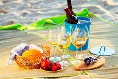 Vidrios del vino blanco en la playa en la puesta del sol, tema de la comida campestre, Fotografía de archivo libre de regalías