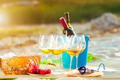 Vidrios del vino blanco en la playa en la puesta del sol, tema de la comida campestre, Imagen de archivo libre de regalías