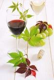 Vidrios del vino rojo, del vino blanco y del manojo de uvas verdes Imagen de archivo libre de regalías