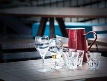 Vidrios del vino y de agua y y un tarro en el café de la calle de Arrowtown Imagen de archivo