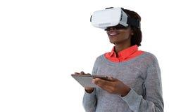 Vidrios del vr de la mujer que llevan joven mientras que usa la tableta Foto de archivo libre de regalías