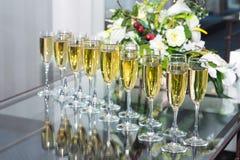 Vidrios elegantes con el champán que se coloca en fila fotografía de archivo