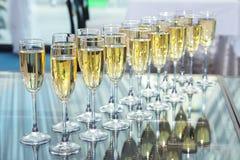 Vidrios elegantes con el champán que se coloca en fila foto de archivo