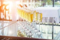 Vidrios elegantes con el champán que se coloca en fila en la tabla durante partido en la puesta del sol imagen de archivo libre de regalías