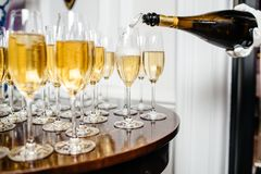 Vidrios elegantes con el champán que se coloca en fila en etiqueta de la porción Imagenes de archivo
