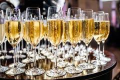Vidrios elegantes con el champán que se coloca en fila en etiqueta de la porción Fotografía de archivo libre de regalías