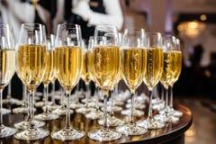 Vidrios elegantes con el champán que se coloca en fila en etiqueta de la porción Foto de archivo libre de regalías