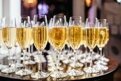Vidrios elegantes con el champán que se coloca en fila en etiqueta de la porción Imagen de archivo