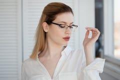 Vidrios elegantes en un marco fino, correcci?n de la visi?n Retrato de una mujer joven fotografía de archivo
