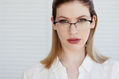 Vidrios elegantes en un marco fino, correcci?n de la visi?n Retrato de una mujer joven fotografía de archivo libre de regalías