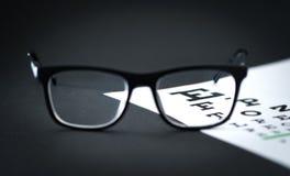 Vidrios en carta de la letra de la prueba del ojo en la tabla del óptico imagenes de archivo