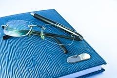 Vidrios en el cuaderno azul con la pluma negra Imagenes de archivo