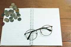 Vidrios en el cuaderno con las monedas ahorro del concepto imagen de archivo libre de regalías