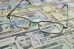 Vidrios en el dinero del dólar, concepto financiero foto de archivo libre de regalías