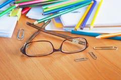 Vidrios en el fondo de lápices y del papel coloreados Fotografía de archivo