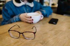 Vidrios en el fondo del café del inconformista de la muchacha en un café Fotografía de archivo