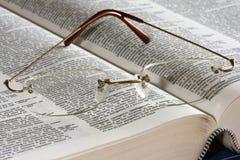Vidrios en el libro abierto Foto de archivo libre de regalías