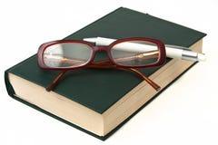 Vidrios en el libro y la pluma Foto de archivo