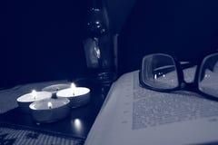 Vidrios en el libro y las velas ardientes fotografía de archivo libre de regalías