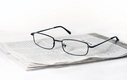 Vidrios en el periódico plegable Foto de archivo libre de regalías