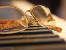 Vidrios en los claves del piano Fotos de archivo libres de regalías