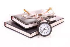 Vidrios en los cuadernos y el reloj aislados Imagen de archivo