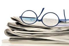 Vidrios en los periódicos fotos de archivo