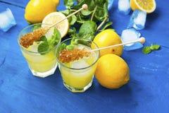 Vidrios frescos de la limonada con los palillos del azúcar, la hierba de la menta y el cubo de hielo Imágenes de archivo libres de regalías