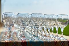 Vidrios hermosos de la tabla del día de fiesta de filas del glassestwo del vino de vidrios en una tabla con tableclothglasses bla Imágenes de archivo libres de regalías