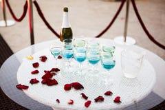Vidrios hermosos del champán en una tabla de cristal y los pétalos de r rojo Imagen de archivo