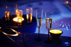 Vidrios iluminados por velas del champán al lado de un Jacuzzi imagen de archivo