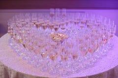 Vidrios llenos de burbujeante o de champán que forma una forma del corazón, colocados en una mesa redonda bajo ligh púrpura de ne Imagenes de archivo