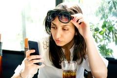 Vidrios morenos agradables del lanzamiento y mirada de smartphone en un café Foto de archivo
