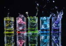 Vidrios multicolores llenados de las bebidas alcoh?licas, con los splases de los cubos de hielo que caen dentro, coloc?ndose en l foto de archivo