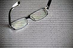 Vidrios negros en un fondo del Libro Blanco con las letras al azar del alfabeto inglés, palabras ocultadas imagen de archivo