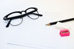 Vidrios negros, Libro Blanco, lápiz, sacapuntas rosados y borrador Fotos de archivo libres de regalías